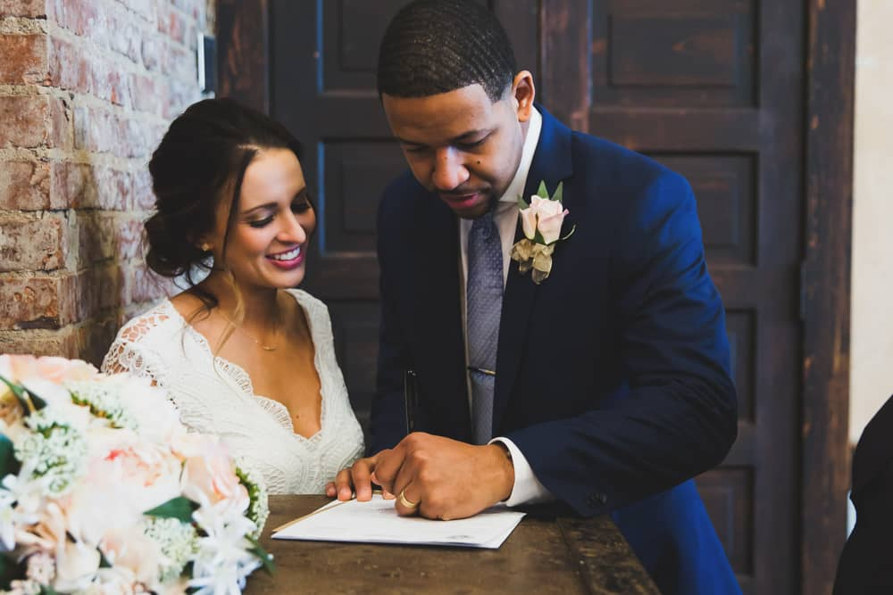 Lindley and Zeke signing their marriage certificate