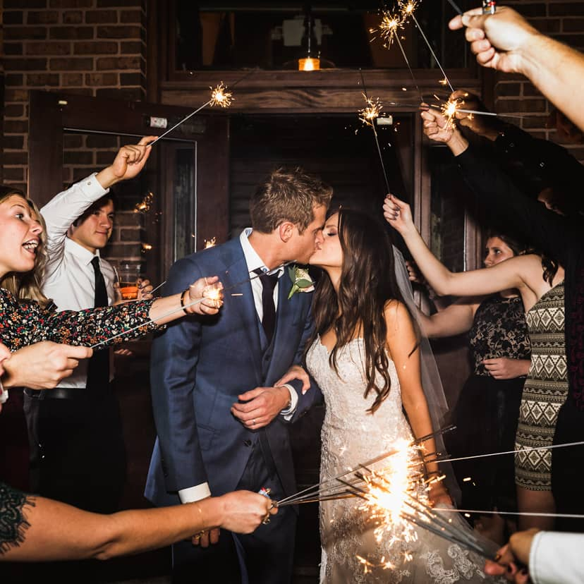 Bride and Groom kiss under a tunnel of sparklers