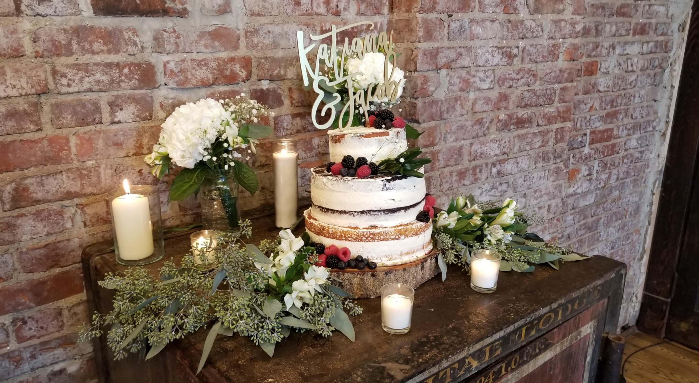 A 3-tiered wedding cake decorated with berries and creme frosting