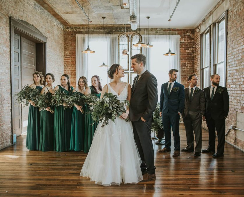 Bride and groom stand in front of their wedding party