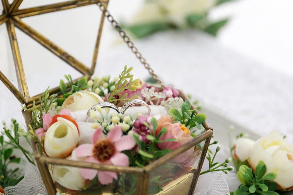 a box of flowers with wedding rings