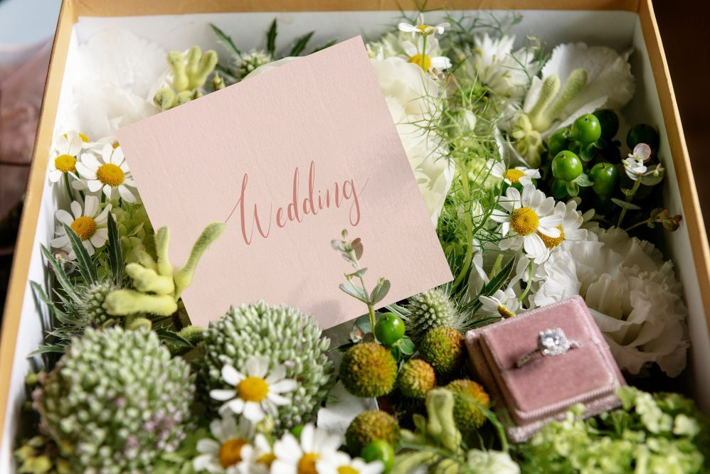 a wedding box with a letter and flowers inside
