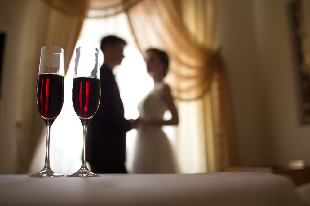 bride and groom with glasses of wine