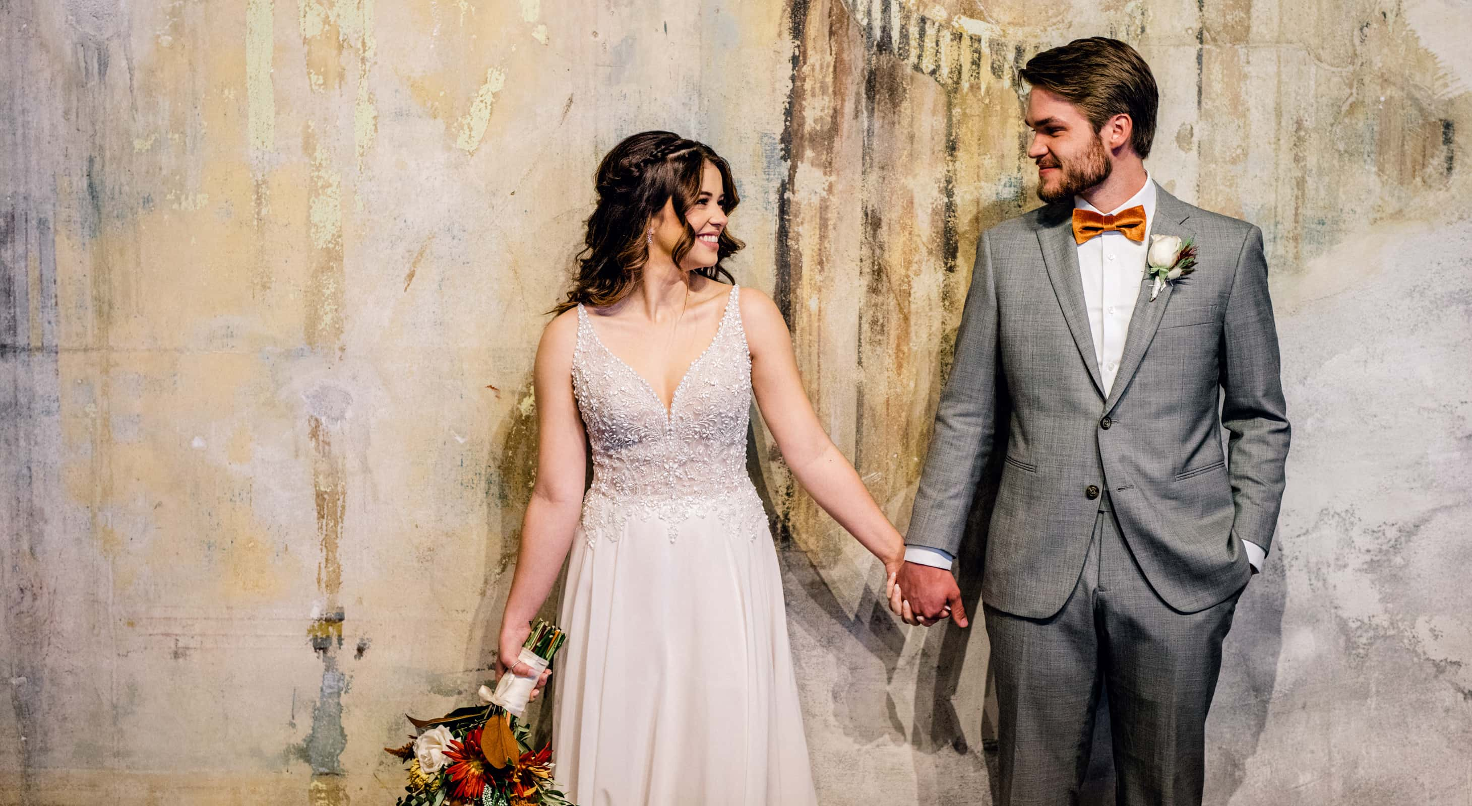 A bride and groom stand in front of a industrial concrete wall