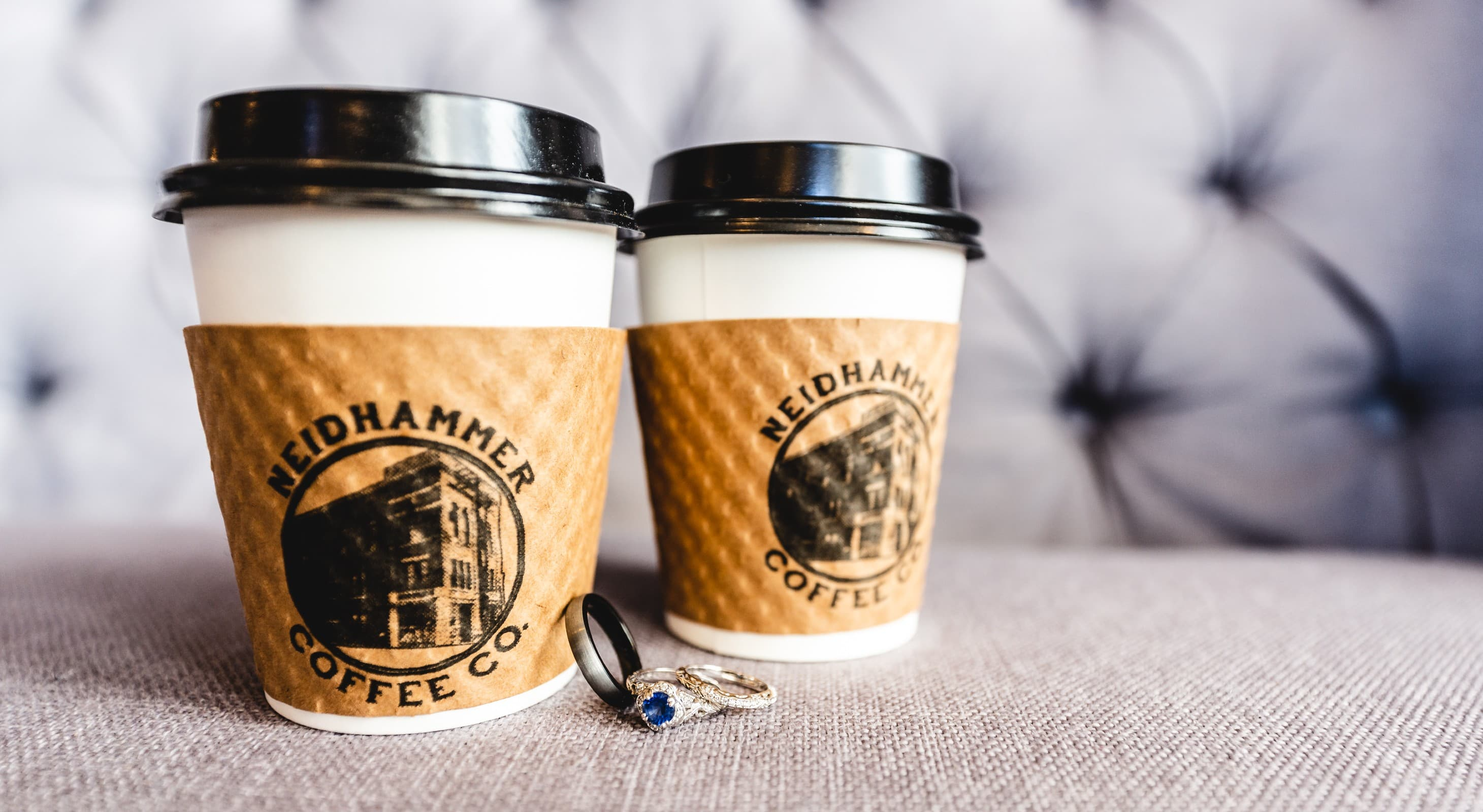 Up close shot of coffee cups and wedding rings