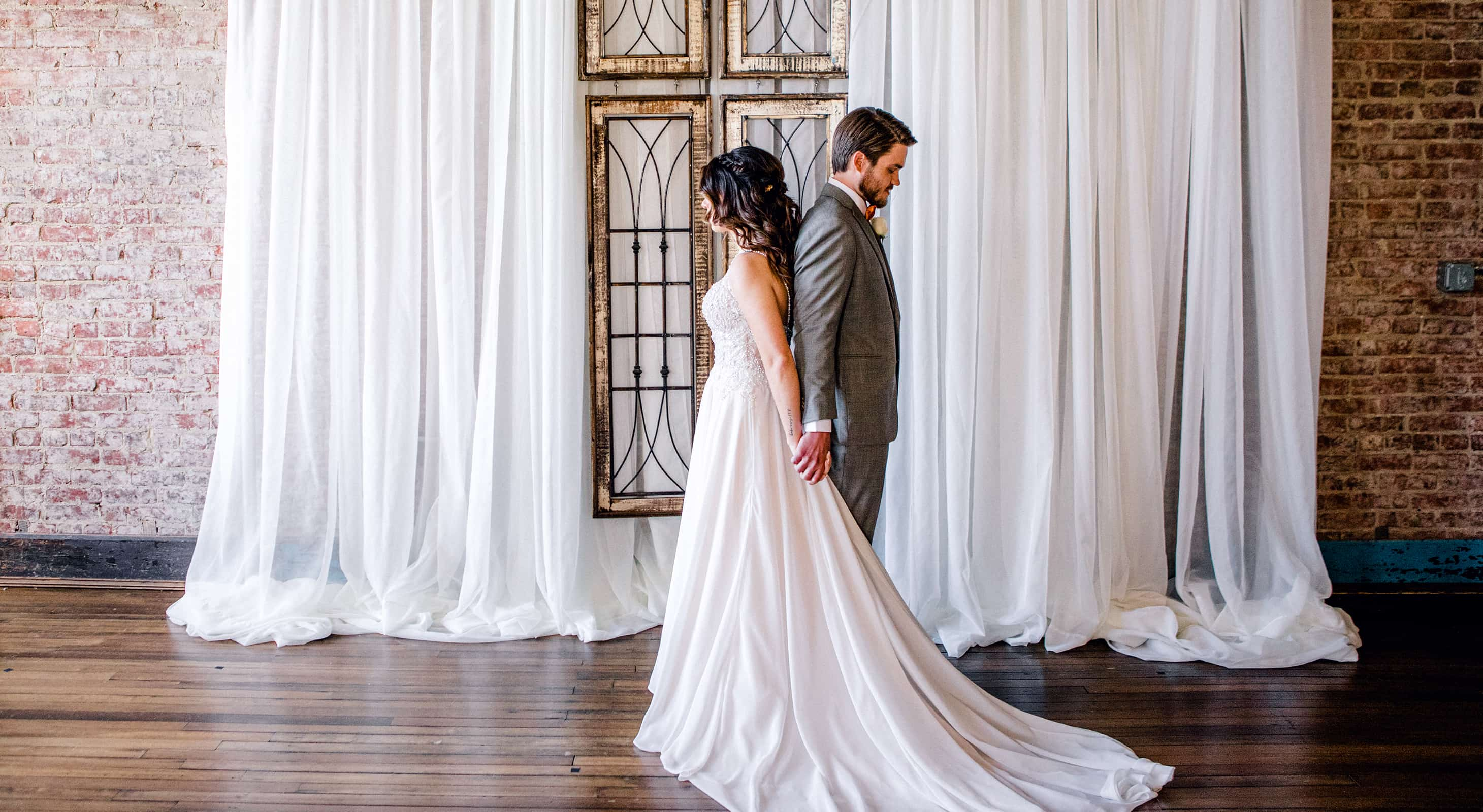 Bride and groom back to back for Blind First Look at our wedding venue in Indianapolis